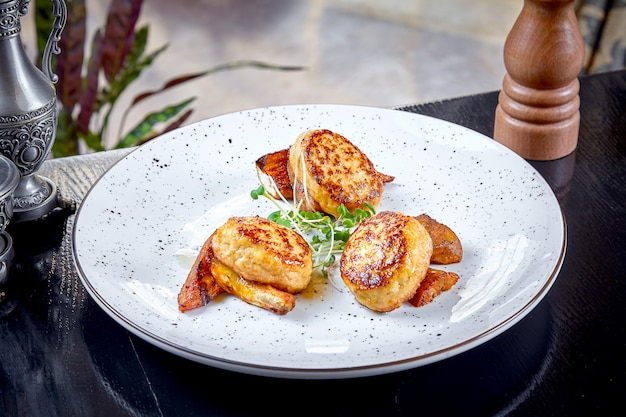 Cucina moderna. chiuda sulla vista sulla cotoletta del servizio del ristorante da coniglio sulla carota arrostita con micro verde sul piatto bianco. concetto di cibo sano. carne grigliata. burger. disteso