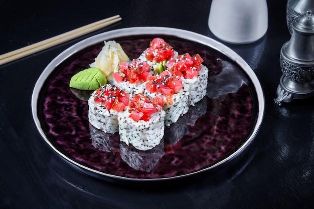 Sushi moderni del rotolo giapponese di cucina in carta di riso. primo piano vista su sushi con avocado e salmone. frutti di mare sani. pesce. dieta, cibo equilibrato. copia spazio. cucina giapponese