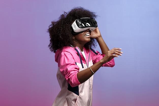 Moderna ragazza dai capelli castani riccia vestita con la giacca sportiva rosa usa gli occhiali per realtà virtuale in studio su sfondo al neon.