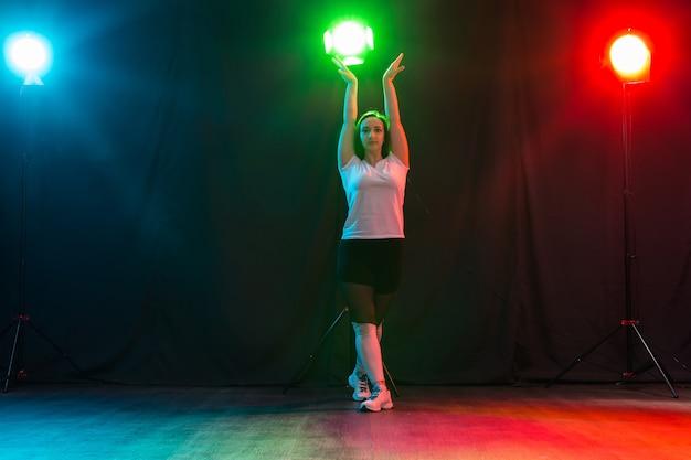 Danza moderna, sport e concetto di persone - giovane donna che balla jazz funk nell'oscurità sotto una luce colorata.