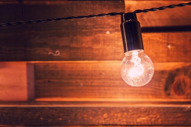 Moderno appartamento di design d'interni in stile classico scuro con lampade retrò appese a sfondo di lampadine. assi di legno con lampade. sala interna decorata con luci dorate. copia spazio mockup poster.