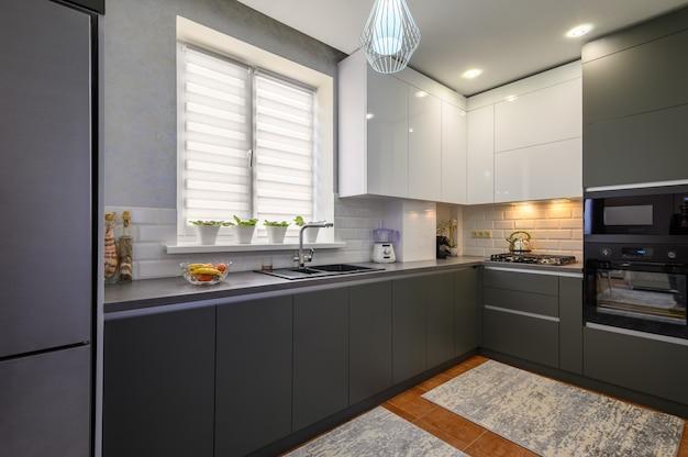 Interiore moderno della piccola cucina grigio scuro