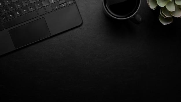 Scrivania moderna in pelle scura con vista dall'alto di sfondo nero tastiera mockup posto