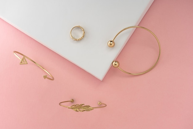 Design moderno bracciali dorati e anello su sfondo rosa e bianco