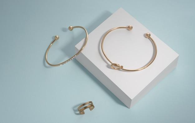 Gioielli d'oro dal design moderno su scatola bianca su sfondo blu con spazio di copia
