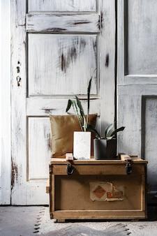 Design moderno del loft interno del soggiorno. pareti in legno grigie con copyspace libero. trend verde in vasi di cemento su una vecchia scatola di legno.