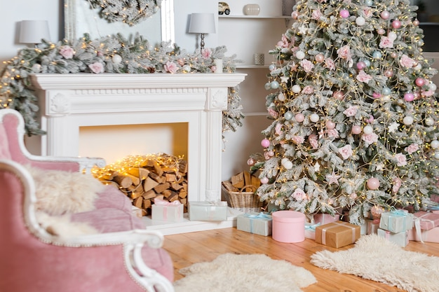 Design moderno della camera con camino in colori chiari decorata con albero di natale ed elementi decorativi, decorazioni di capodanno, buone vacanze invernali, albero di natale e regali.