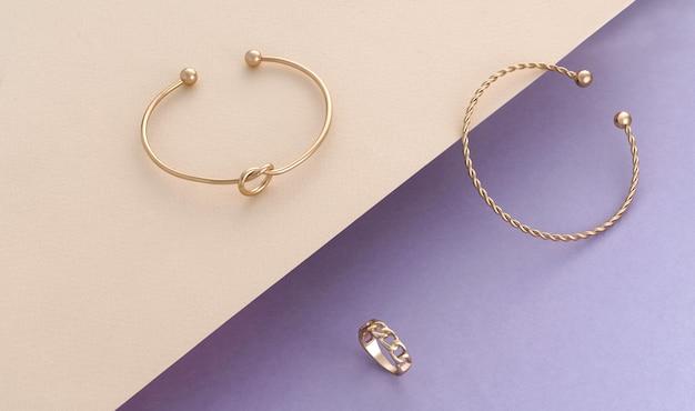 Braccialetti e anello dorati a forma di spirale e nodo dal design moderno su carta beige e viola