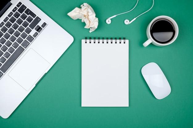 Tavolo da ufficio design moderno con pagina di quaderno bianco, computer portatile e tazza di caffè
