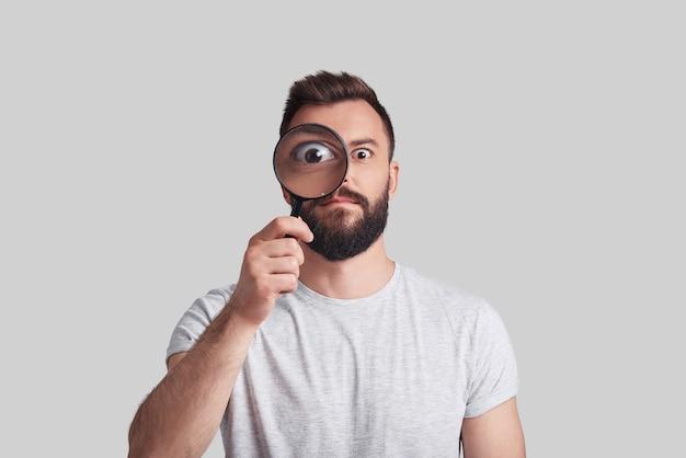 Detective moderno. giovane allegro che applica la lente d'ingrandimento mentre sta in piedi su uno sfondo grigio