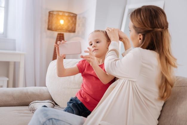 Dispositivo moderno. carina piacevole bella ragazza seduta sul divano e che tiene uno smartphone pur avendo fatto la sua acconciatura