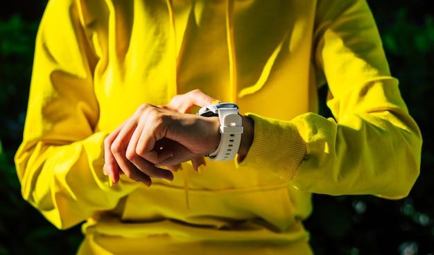 Dispositivo moderno. una ragazza con una felpa con cappuccio gialla e unghie gialle, con un moderno smartwatch bianco in mano, che fa clic sul touch screen.