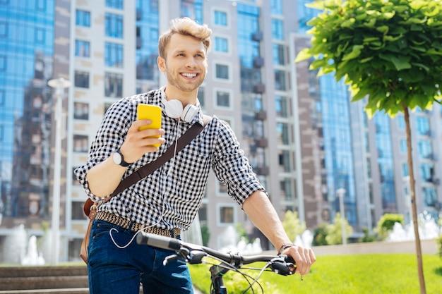 Dispositivo moderno. uomo bello positivo che tiene il suo smartphone mentre va in bicicletta