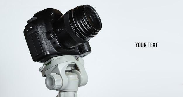 Moderna fotocamera digitale con un treppiede su sfondo grigio. astrofotografia. copia spazio