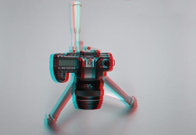 Moderna fotocamera digitale con treppiede su sfondo grigio. effetto glitch. vista dall'alto