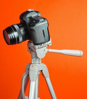 Moderna fotocamera digitale con un treppiede su sfondo arancione