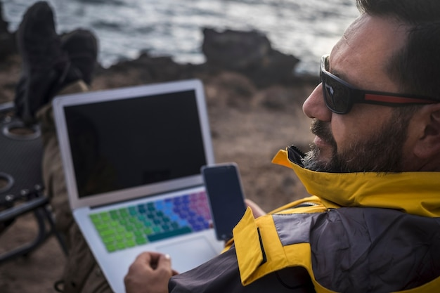 Moderno viaggiatore nomade digitale uomo barbuto lavora con telefono cellulare e laptop all'aperto di fronte all'oceano