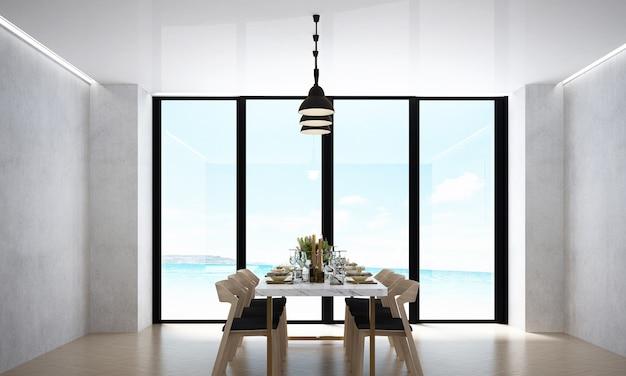 La moderna sala da pranzo e la decorazione dei mobili, lo sfondo del muro bianco e la vista sul mare
