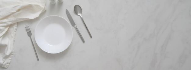 Tavolo da pranzo moderno con piatto, argenteria, tovagliolo, bottiglie di condimento e copia spazio sulla scrivania di marmo