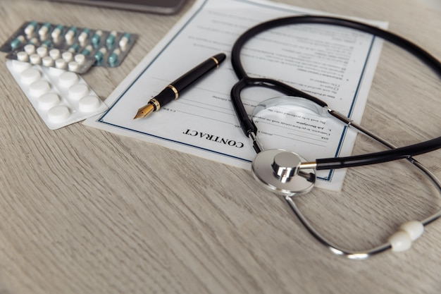 Scrivania moderna del medico. stetoscopio con pillole e contratto sanitario sul primo piano tavolo in legno