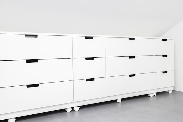 Cassettiera moderna con molto spazio di archiviazione in una stanza di una casa. copia spazio