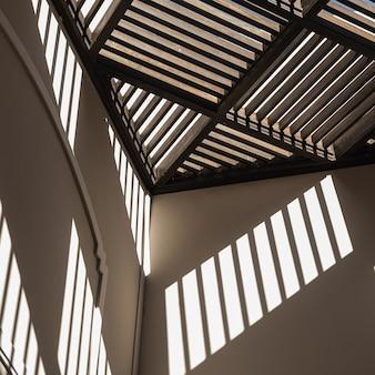 Moderno edificio in stile orientale con pareti beige e ombre di luce solare sui muri.