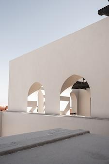 Moderno edificio in stile orientale con pareti beige, finestre e ombre della luce solare su rotaia