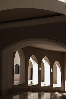 Moderno edificio in stile orientale con finestre e ombre di luce solare su pareti beige
