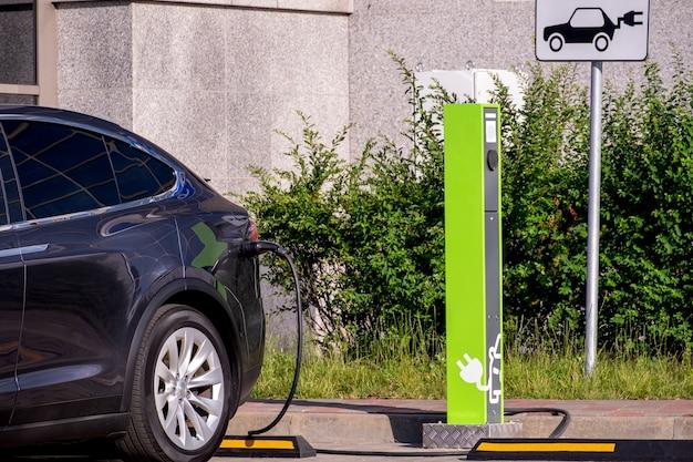 Moderna auto elettrica sul punto di ricarica davanti agli edifici per uffici