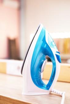 Ferro da stiro elettrico moderno sull'asse da stiro su priorità bassa della camera di trucco.