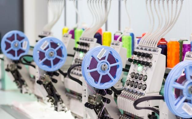 Moderna macchina da ricamo con dispositivo per cucire paillettes e fili colorati in produzione.