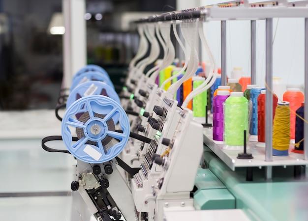 Moderna macchina da ricamo con dispositivo per cucire paillettes e fili colorati.