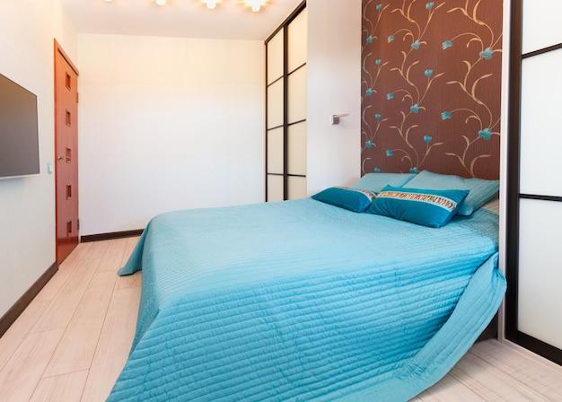 Moderna camera da letto vuota con letto matrimoniale blu
