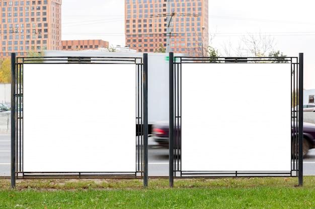 Insegne in bianco vuote moderne dei tabelloni per le affissioni di pubblicità in una città all'aperto.