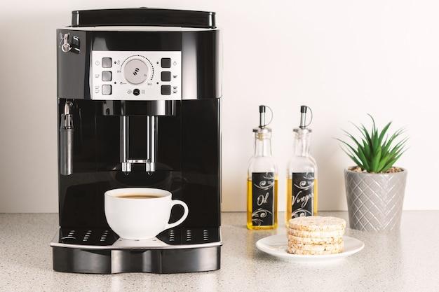 Moderna macchina per caffè espresso con una tazza all'interno del primo piano della cucina.