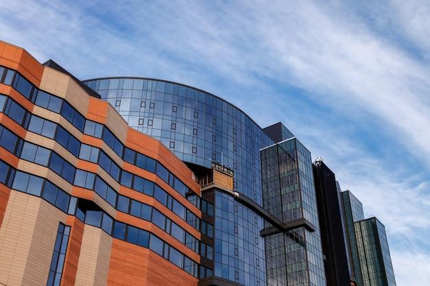 La facciata moderna dell'edificio per uffici è un frammento astratto, con finestre lucide in una struttura d'acciaio. ottimo sfondo per un biglietto da visita, un volantino, un banner con spazio per un'iscrizione o un logo