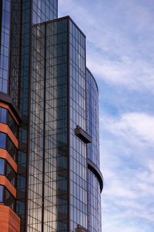 La facciata moderna dell'edificio per uffici è un frammento astratto, con finestre lucide in una struttura in acciaio.