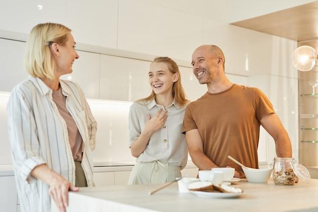 Famiglia moderna che ride felicemente mentre si gusta la colazione insieme in piedi a tavola in cucina interna
