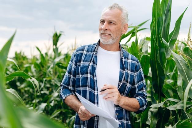 L'agricoltore moderno lavora in un campo di grano, tenendo i documenti nelle sue mani