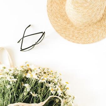 Concetto di moda moderna con cappello di paglia, bouquet di fiori di camomilla margherita in sacchetto di stringa e bicchieri