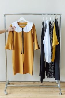 Vestiti moderni dello stilista che appendono sulla rotaia