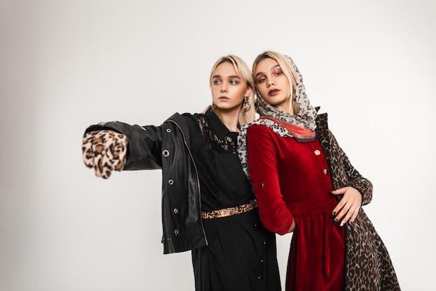 Giovani donne alla moda moderne con capelli biondi con labbra sexy in bei vestiti eleganti alla moda che posano all'interno