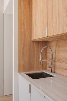 Rubinetto moderno e lavello in cucina elegante con mobili in legno interni in stile minimalista in refurbis...
