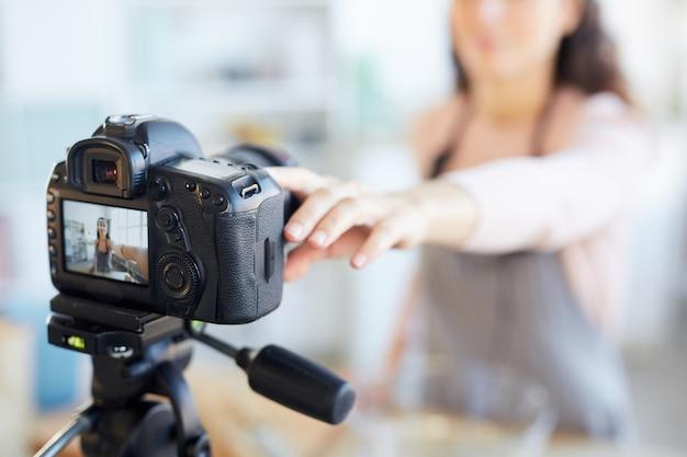 Moderna blogger di cibo femminile che imposta la sua fotocamera prima dell'inizio delle riprese, fotocamera orizzontale a fuoco