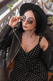 La donna femminile moderna in cappello alla moda in vestito nero lussuoso in giacca di pelle raddrizza gli occhiali da sole. la ragazza affascinante del modello di moda in vestito d'annata alla moda nero sta riposando sulla sedia in caffè.