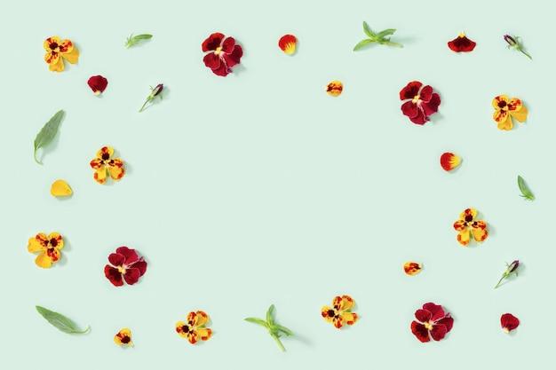 Moderna cornice floreale con fiori gialli e rossi viola del pensiero, piccolo piatto estivo floreale laico stile stagionale con spazio di copia.