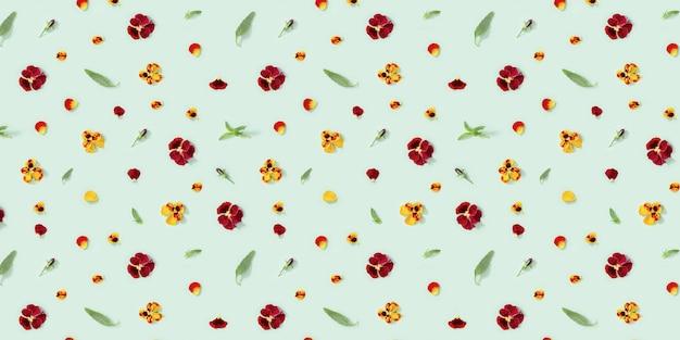 Motivo floreale moderno con fiori viola del pensiero gialli e rossi, foglie verdi, boccioli. petali, piccolo ornamento floreale stagionale estivo.