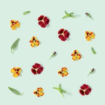Motivo floreale moderno con fiori viola del pensiero gialli e rossi, foglie verdi, ornamento per lo styling stagionale