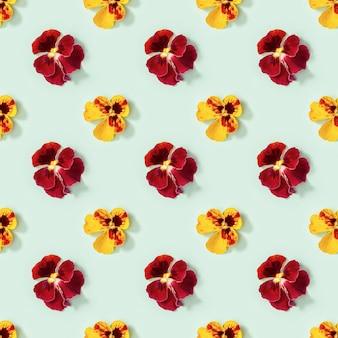 Motivo floreale moderno senza cuciture con fiori viola del pensiero gialli e rossi piccola estate fiorita stagionale