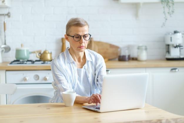 Moderna scrittrice donna matura focalizzata che indossa occhiali digitando qualcosa sul laptop che lavora online